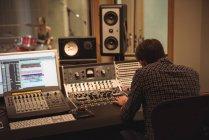 Visão traseira do engenheiro de áudio usando misturador de som no estúdio de gravação — Fotografia de Stock