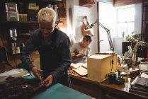 Внимательная ремесленница режет кожу в мастерской — стоковое фото