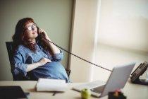 Femme d'affaires enceinte touchant le ventre tout en parlant au téléphone au bureau — Photo de stock