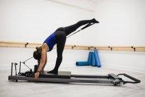 Donna che allunga le gambe sul riformatore in palestra — Foto stock