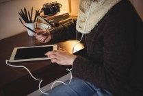 Partie médiane de la femme écoutant de la musique sur tablette numérique à la maison — Photo de stock