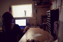 Peluquería femenina usando portátil en tienda dreadlocks - foto de stock