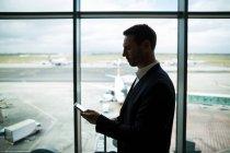 Empresário com bagagem usando telefone celular no aeroporto — Fotografia de Stock