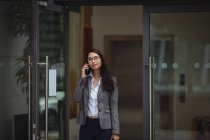 Businesswoman talking on mobile phone outside office building — Stock Photo
