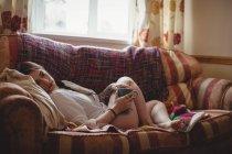 Женщина держит чашку кофе и лежит дома на диване — стоковое фото