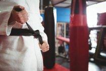 Средняя секция игрока в карате, завязывающего пояс в фитнес-студии — стоковое фото