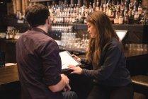 Пара обговорювати над менюВ барна стійка — стокове фото