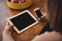 Mujer usando teléfono móvil y tableta digital en la sala de estar en casa - foto de stock