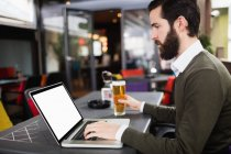 Man using laptop while having glass of beer in bar — Stock Photo