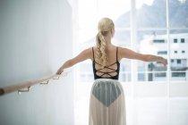 Балерина розтягування Барре під час практикуючим балету танцю в студії — стокове фото