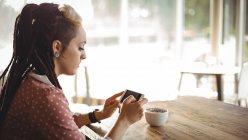Женщина с помощью мобильного телефона в кафе — стоковое фото