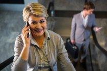 Деловая женщина на эскалаторе разговаривает по мобильному телефону в аэропорту — стоковое фото