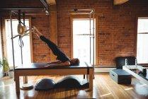 Vista lateral da mulher praticando pilates em equipamentos de estúdio de fitness — Fotografia de Stock