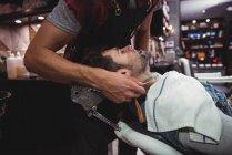 Cliente recebendo barba raspada com navalha na barbearia — Fotografia de Stock