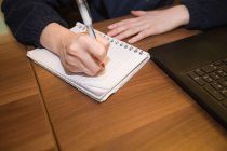 Close-up of woman sitting at desk and writing on notebook in office — Stock Photo