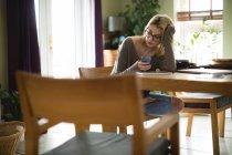 Femme utilisant un téléphone portable tout en étant assis à la maison — Photo de stock