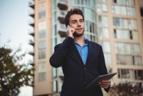 Businessman talking on mobile phone and holding digital tablet near office building — Stock Photo