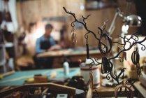 Vários acessórios de couro pendurados em ganchos na oficina — Fotografia de Stock