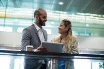 Pareja sonriente interactuando con todos o en la sala de espera en la terminal del aeropuerto - foto de stock