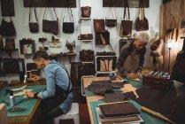 Внимательные ремесленницы молотят кожу в мастерской — стоковое фото