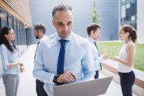 Geschäftsmann benutzt Laptop vor Bürogebäude — Stockfoto