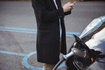 Средняя часть человека с помощью мобильного телефона во время зарядки автомобиля на электростанции зарядки автомобиля — стоковое фото