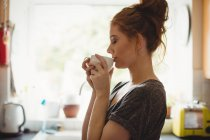 Beautiful woman having coffee in kitchen at home — Stock Photo