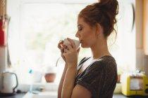 Женщина, пьющая кофе на кухне дома — стоковое фото
