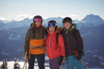 Three female skiers standing together in snow covered mountains — Stock Photo