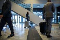 Gente de negocios caminando con equipaje en la zona de espera en el aeropuerto - foto de stock