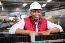 Портрет усміхнений чоловік співробітника стоячи конвеєра на заводі — стокове фото