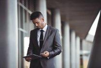 Uomo d'affari che utilizza tablet digitale e telefono cellulare nel campus dell'ufficio — Foto stock