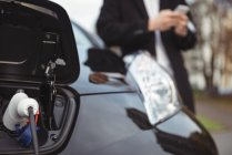 Close-up of electric car getting charged — Stock Photo