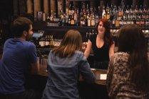Бармен, взаимодействующий с клиентами за барной стойкой — стоковое фото
