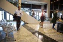 Empresário usando seu telefone enquanto caminha no terminal do aeroporto — Fotografia de Stock