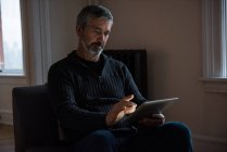 Человек, использующий цифровой планшет в гостиной на дому — стоковое фото