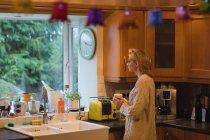 Donna che tiene una tazza di caffè in cucina a casa — Foto stock