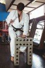 Каратист разбивает бетонный блок в фитнес-студии — стоковое фото