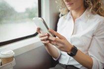 Vista ritagliata della donna d'affari che utilizza lo smartphone durante il viaggio — Foto stock
