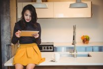 Woman sitting on kitchen worktop using digital tablet at home — Stock Photo