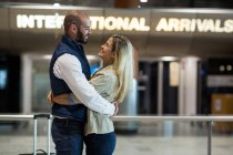 Cheerful couple embracing each other in waiting area at airport terminal — Stock Photo