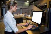 Female staff working on security desk in the airport terminal — Stock Photo