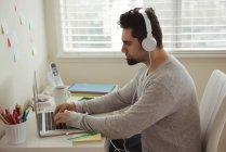 Вид сбоку человека в наушниках, сидящего за рабочим столом с ноутбуком — стоковое фото