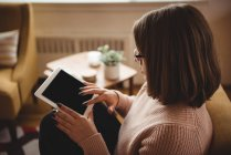 Женщина сидит на стуле с помощью цифрового планшета в гостиной на дому — стоковое фото