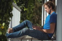 Man sitting on porch and using mobile phone — Stock Photo