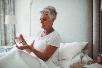 Femme âgée prenant des médicaments dans la chambre à coucher à la maison — Photo de stock