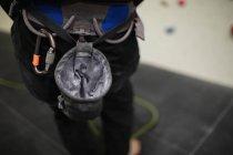 Partie médiane de l'homme debout contre un mur d'escalade artificiel dans la salle de gym — Photo de stock