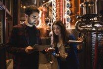 Чоловік і жінка, обговорюючи над цифровий планшетний пивоварного заводу — стокове фото