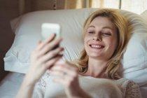 Женщина лежит на кровати и пользуется мобильным телефоном в спальне дома — стоковое фото