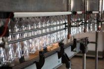 Ряд пустых бутылок на производственной линии на заводе холодных напитков — стоковое фото